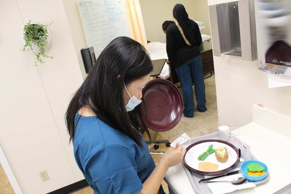 Learn More Fast student preparing fake meal for a mannequin patient