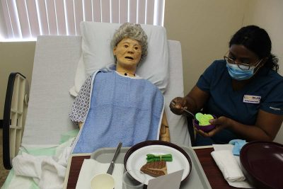 Learn More Fast student feeding a mannequin patient.