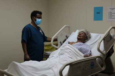 Learn More Fast student learning how to operate hospital bed.