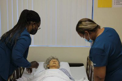 Learn More Fast students working with a mannequin on a bed