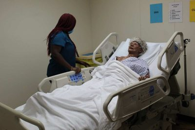 Learn More Fast student working with a mannequin on a hospital bed.