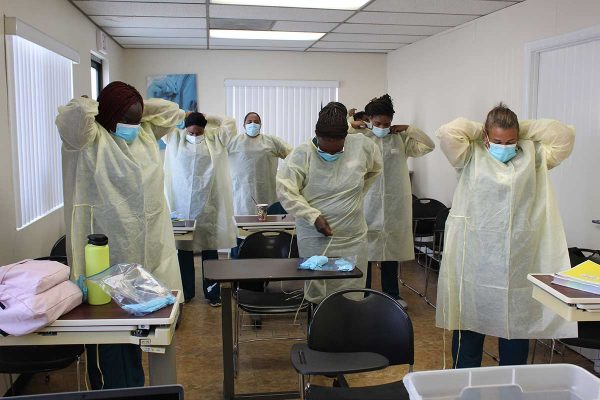 Learn More Fast students gearing up with masks and gowns.